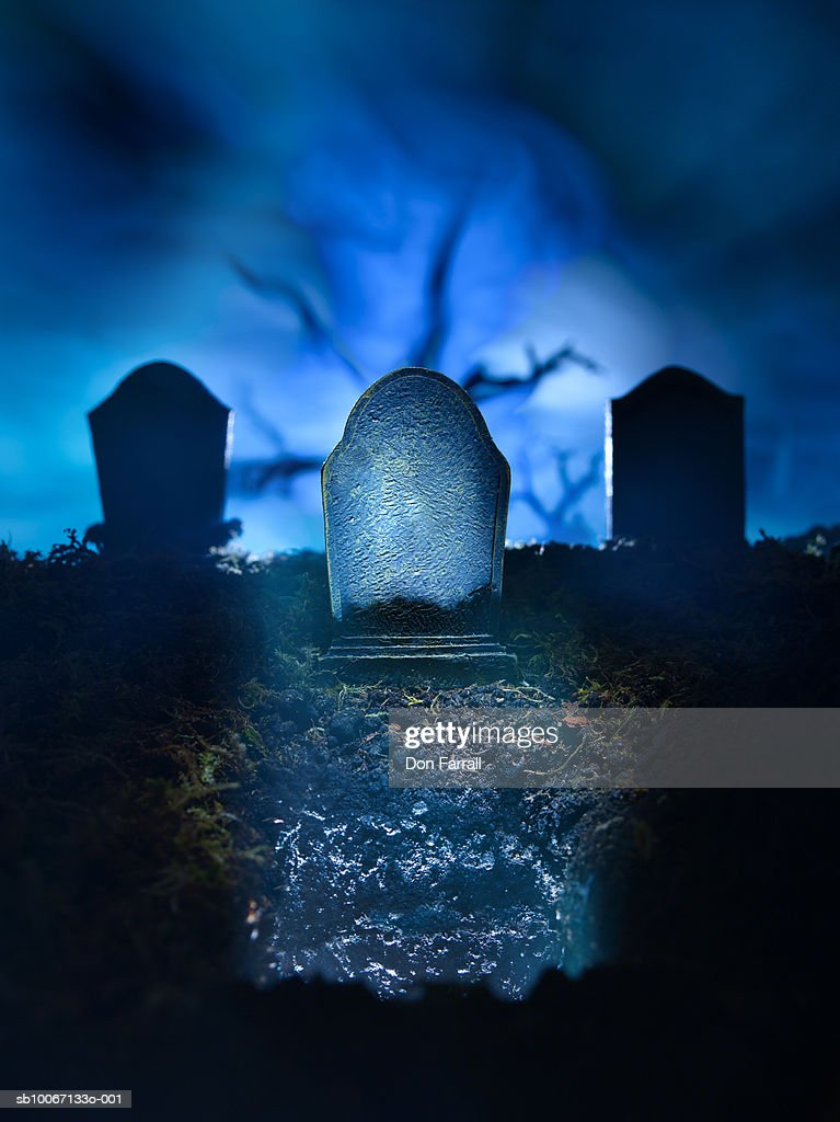 light in fresh grave and blank tombstone stock photo
