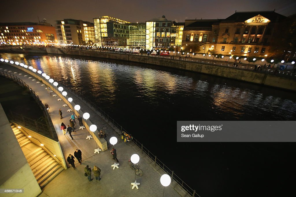 A light installation of balloons tethered to lamps illuminates the course of the Berlin Wall along the Spree River two days before the 25th...