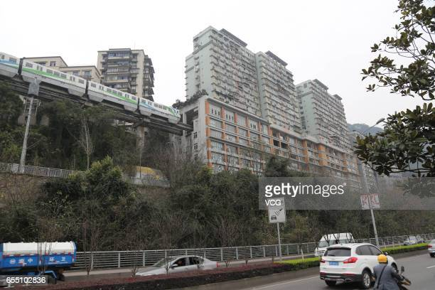 A light railway train passes through a residential building on March 18 2017 in Chongqing China Chongqing Rail Transit No2 and a 19storey residential...