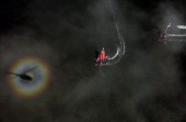 Light refracts off fog creating a rainbow halo around a helicopter shadow while Emirates Team New Zealand skippered by Dean Barker races against...