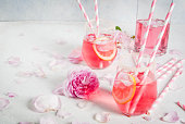 Summer refreshment drinks. Light pink rose cocktail, with rose wine, tea rose petals, lemon. On a white stone concrete table. With striped pink tubules, petals and rose flowers. Copy space