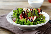 Light salad with figs, lettuce and balsamic sauce in  white bowl, healthy food