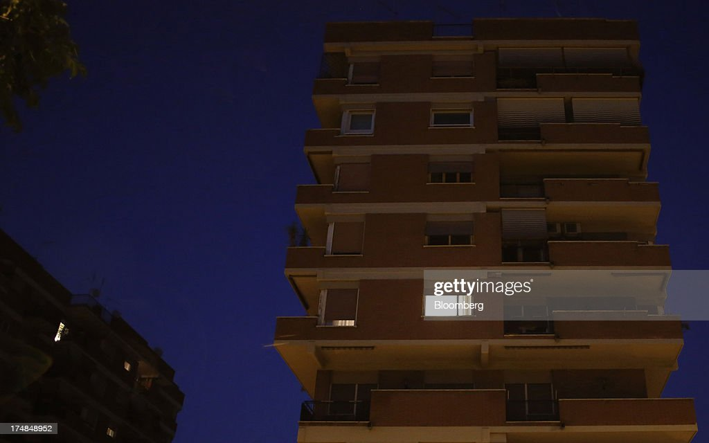 Light shines from a window of a residential apartment building in Rome, Italy, on Saturday, July 27, 2013. Italy's home prices are low enough to trigger an increase in purchases for the first time since 2006, though that won't lift values for at least two years, according to the Nomisma institute. Photographer: Alessia Pierdomenico/Bloomberg via Getty Images