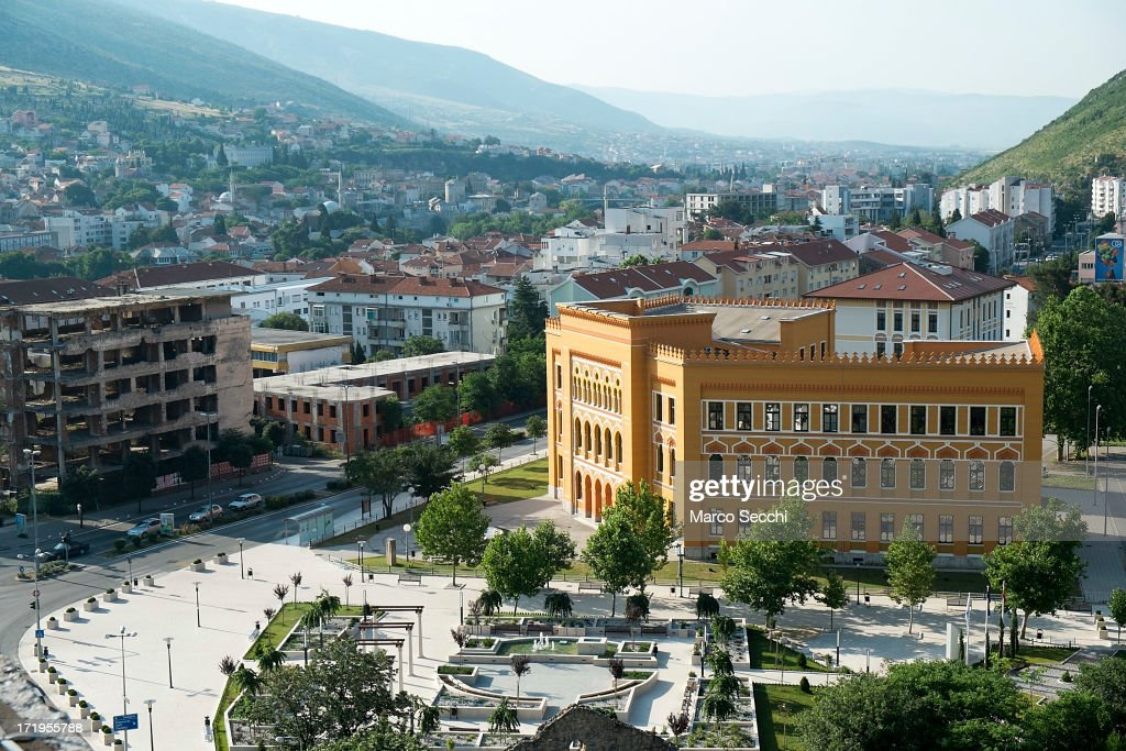 Light shines over the Spanish Square with a newly refurbished building near an old derelict one as the city of Mostar remembers the 1993 conflict on June 28, 2013 in Mostar, Bosnia and Herzegovina. The Siege of Mostar peaked in 1993 during the Croat-Bosniak conflict lasting eighteen months as fighting took place as Bosnia and Herzegovina declared independence from Yugoslavia. The city was divided in half between the two battling armies. Mostar, dating back over four hundred years, was mostly destroyed through the fighting. Although reconstruction has slowly commenced in the last decades, evidence of the war remains in bullet ravaged buildings still standing throughout the city.