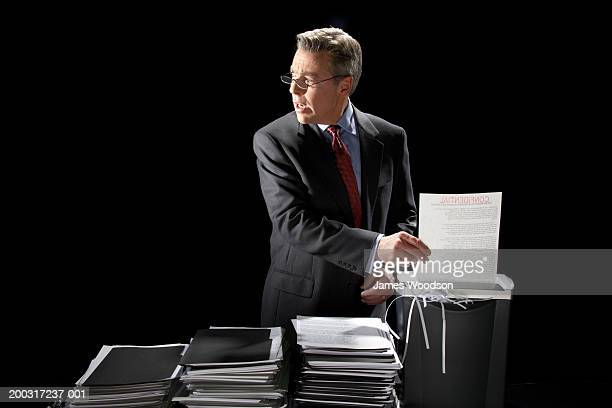 Light shining on mature businessman shredding document