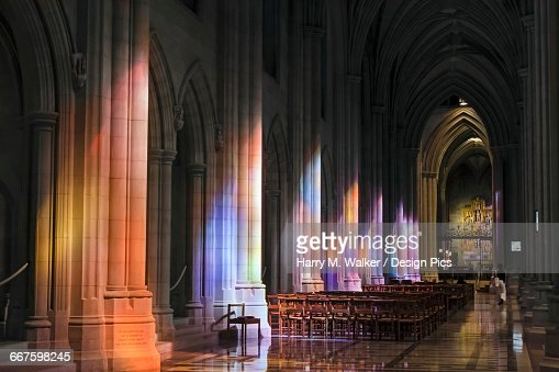 Light streaming through stained glass windows with colourful light columns along the cathedral nave, altarpiece in St. Marys Chapel visible background