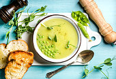 Light summer green pea cream soup in bowl with sprouts, bread toasts and spices. White ceramic board in the center, turquoise blue wooden background. Top view