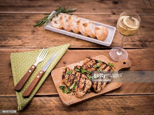 Light summer meal of pork fillets, sliced baguette and wine