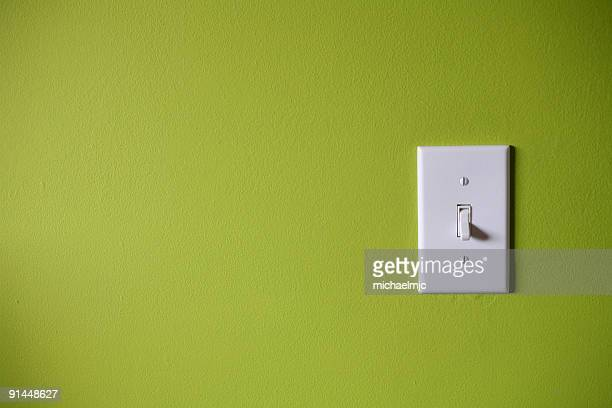 Light switch in front of green background