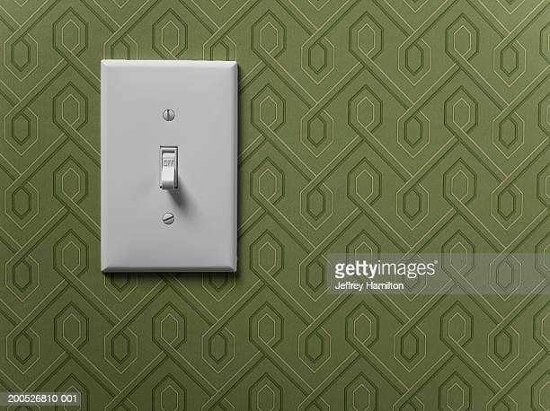 Light switch on green wallpapered wall, close-up