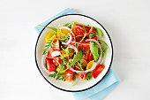 light tomato salad with arugula top view