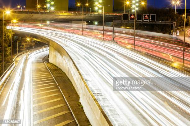 Light tracks of driving cars on a motorway autobahn at night on November 7 in Berlin Germany Daily rushhour traffic