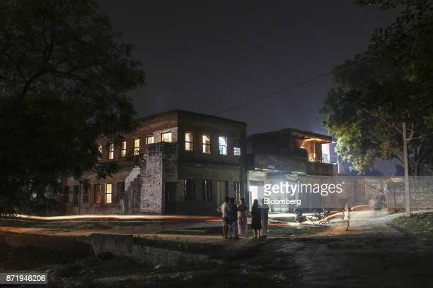 A light trail is left by a cyclist as people stand outside handloom workshops at night in Varanasi Uttar Pradesh India on Friday Oct 27 2017 In...