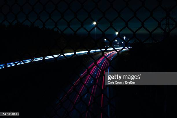 Light Trail On Highway Seen Through Chainlink Fence At Night