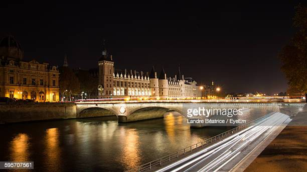 Light Trails By Arch Bridge Over River In Illuminated City Against Clear Sky At Night