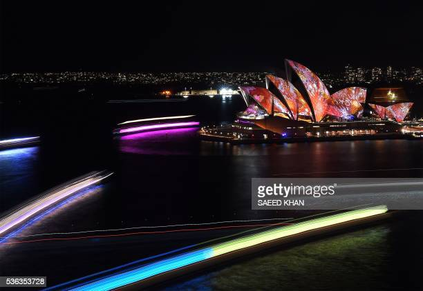 Light trails from boats during a long exposure are seen as Australia's iconic Opera House is lit up for the Vivid Sydney festival on June 1 2016...