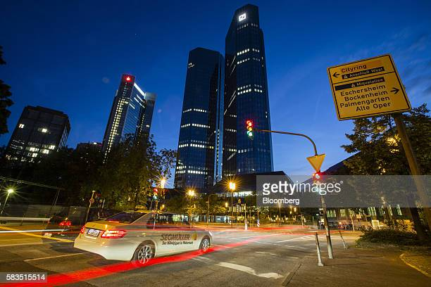 Light trails from passing traffic illuminate a road as the twin tower skyscraper headquarter offices of Deutsche Bank AG stand at night in Frankfurt...