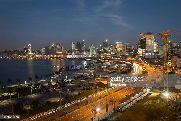 Light trails from passing traffic illuminate the promenade at night beneath a construction crane in Luanda Angola on Friday Nov 8 2013 Angola the...