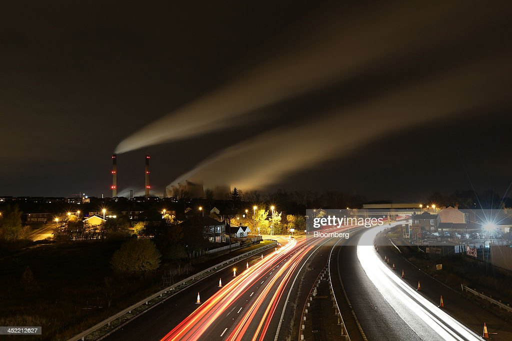 Light trails from passing traffic illuminates a road as vapour is seen escaping from the chimneys of Ferrybridge coal fired power station, operated by SSE Plc, in Ferrybridge, U.K., on Tuesday Nov. 26, 2013. SSE Plc, the U.K.'s second-biggest energy supplier, pledged to curb increases in customer bills if the government cuts environmental levies that push up tariffs. Photographer: Chris Ratcliffe/Bloomberg via Getty Images