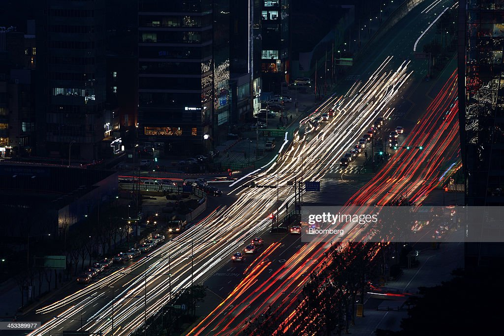 Light trails left by moving traffic run along a road in this long exposure photograph taken in the Gangnam district in Seoul, South Korea, on Monday, Dec. 2, 2013. South Korea's economy will grow 3.9 percent next year - the fastest pace since 2010 - after a 2.8 percent expansion in 2013, the finance ministry projected in September. Photographer: SeongJoon Cho/Bloomberg via Getty Images