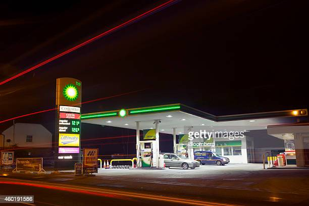 Light trails made by passing automobiles are seen as vehicles stand at fuel pumps at a gas station operated by BP Plc in Guildford UK on Monday Dec 8...