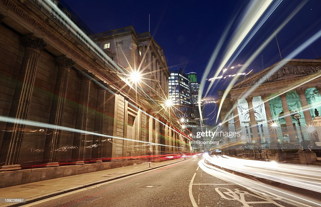 Light trails made by passing vehicles are seen between the Bank of England (BOE), left, and the Royal Exchange, right, in London, U.K., on Wednesday, Jan. 9, 2013. Bank of England policy makers will probably refrain from adding further stimulus to the U.K. economy today as their new credit-boosting program shows early signs of success. Photographer: Chris Ratcliffe/Bloomberg via Getty Images