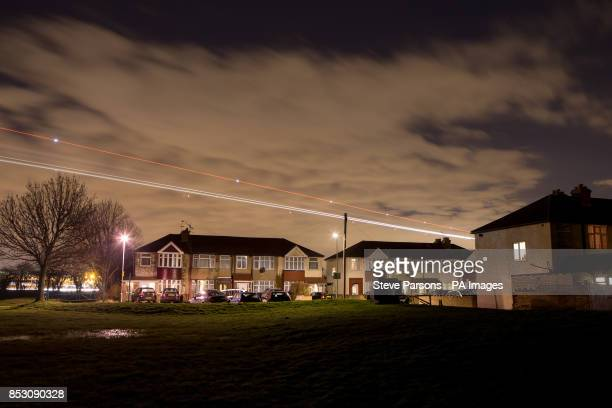 Light trails of a plane flying over houses in the village of Bedfont Greater London as it comes into land at Heathrow Airport