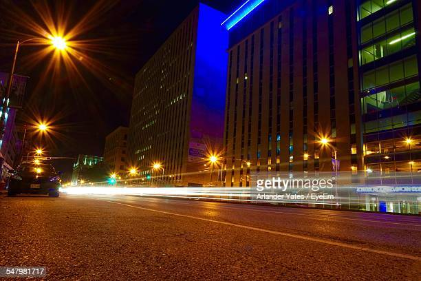 Light Trails On Street Against Buildings At Night