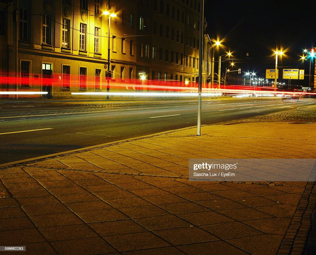 Light Trails Over Street Against Buildings In City