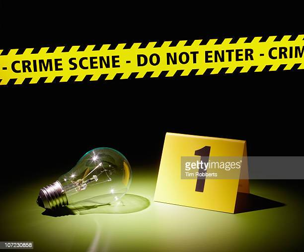 Lightbulb with crime scene tape and number.
