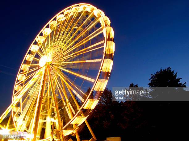 Lighted ferris wheel spinning in motion at night