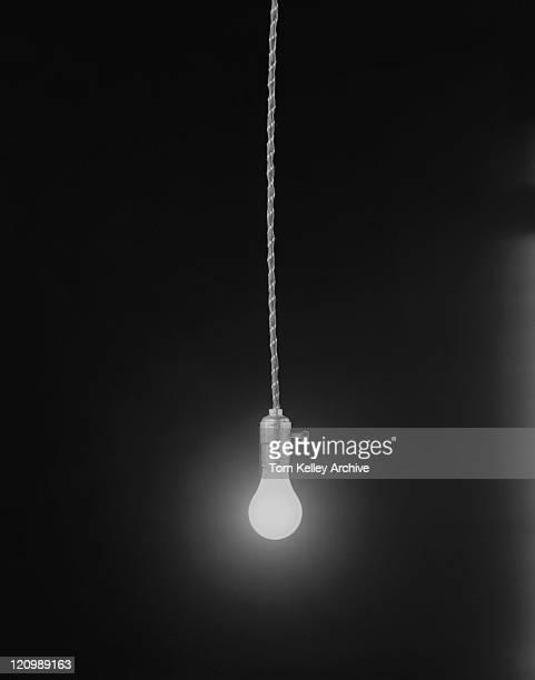 Lighted light bulb on black background