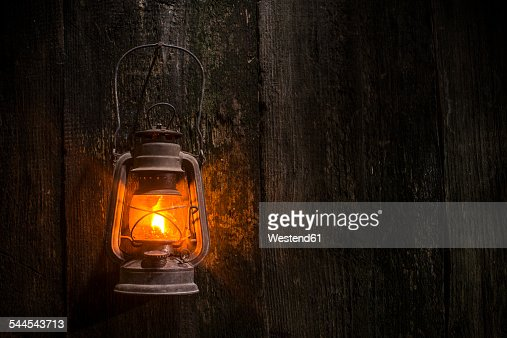 Lighted old gas lantern hanging on wooden wall