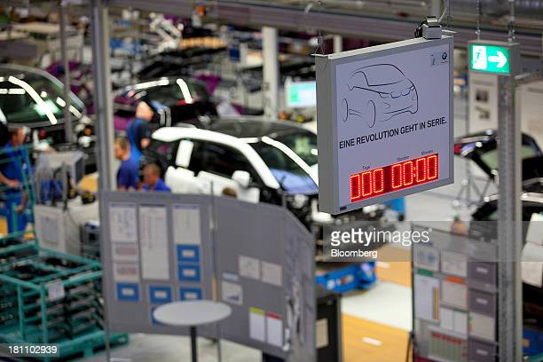 A lightemitting diode clock sits above the Bayerische Motoren Werke AG factory floor in Leipzig Germany on Wednesday Sept 18 2013 BMW is expanding...