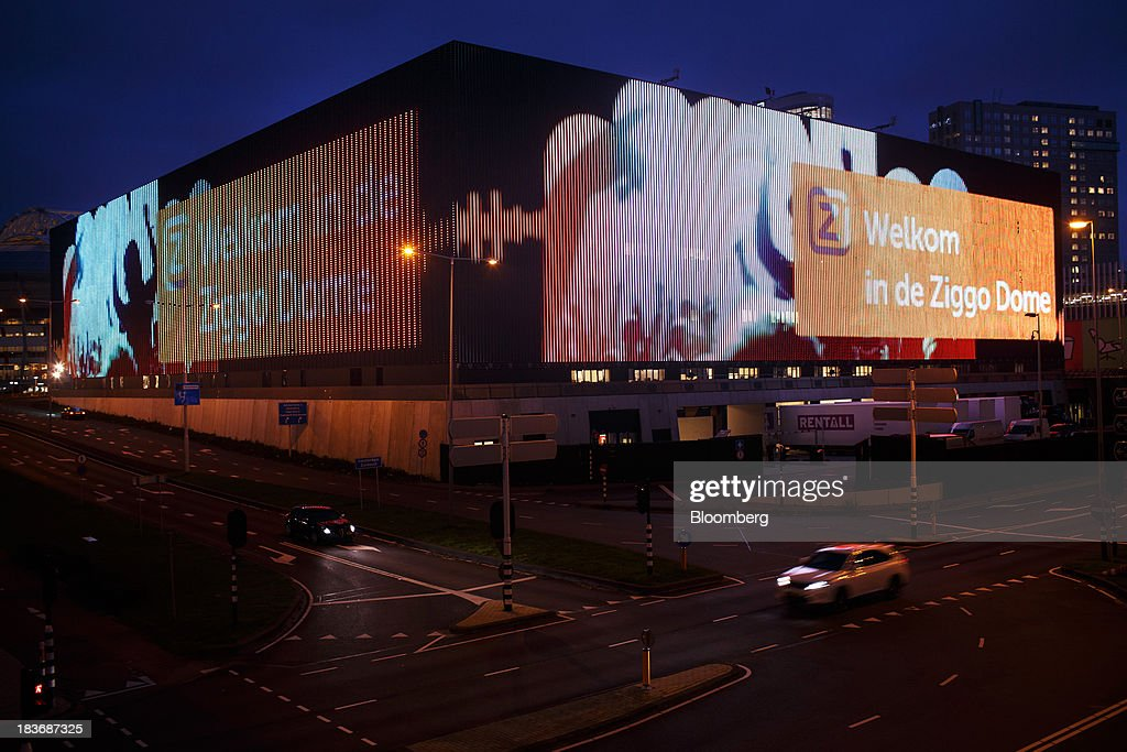 A light-emitting diode (LED) display illuminates the Ziggo Dome entertainment arena as automobiles pass at night in Amsterdam, Netherlands, on Tuesday, Oct. 8, 2013. Cable-TV provider Ziggo NV, which is 28.5 percent owned by Liberty Global Plc, is pushing into the Dutch mobile market with low-priced packages, following a playbook pioneered by French discount operator Iliad SA. Photographer: Jasper Juinen/Bloomberg via Getty Images