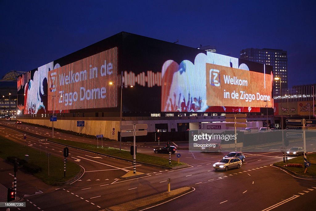 A light-emitting diode (LED) display sits illuminated on entertainment arena Ziggo Dome as automobiles pass at night in Amsterdam, Netherlands, on Tuesday, Oct. 8, 2013. Cable-TV provider Ziggo NV, which is 28.5 percent owned by Liberty Global Plc, is pushing into the Dutch mobile market with low-priced packages, following a playbook pioneered by French discount operator Iliad SA. Photographer: Jasper Juinen/Bloomberg via Getty Images