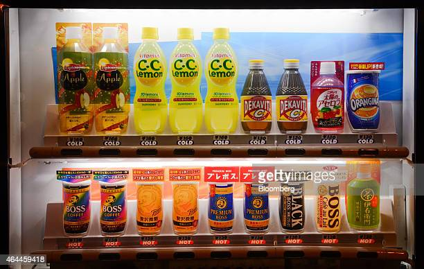 Lightemitting diodes illuminate cans and bottles of soft drinks displayed for sale in a Suntory Beverage Food Ltd vending machine in Tokyo Japan on...