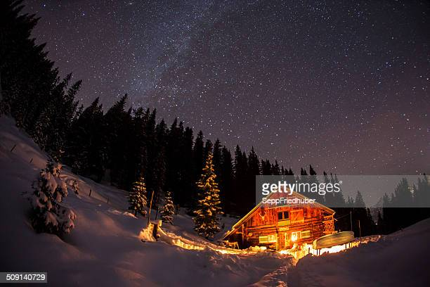 Lightened mountain hut in the austrian alps with milky way