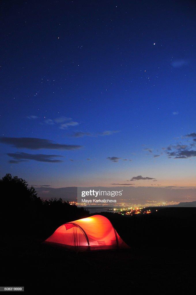 Lightened tent at nigh over city lights