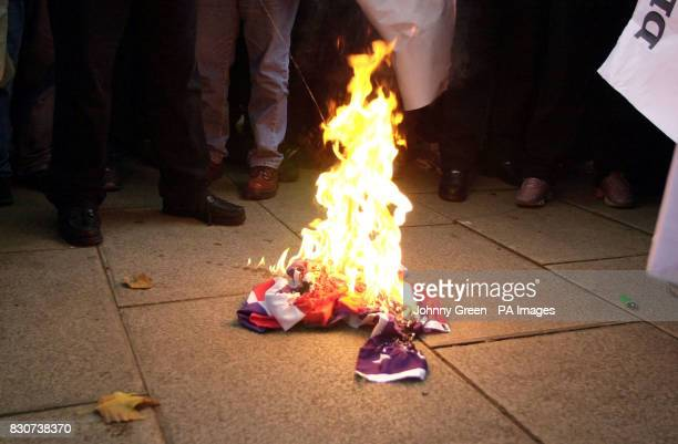 Lighterfuel is poured onto an alreadyablaze American flag at a demonstration against the USled bombings of Afghanistan outside the London Central...
