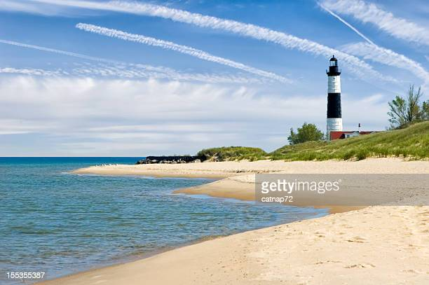 Lighthouse and Beach in Summer with Dramatic Sky Background