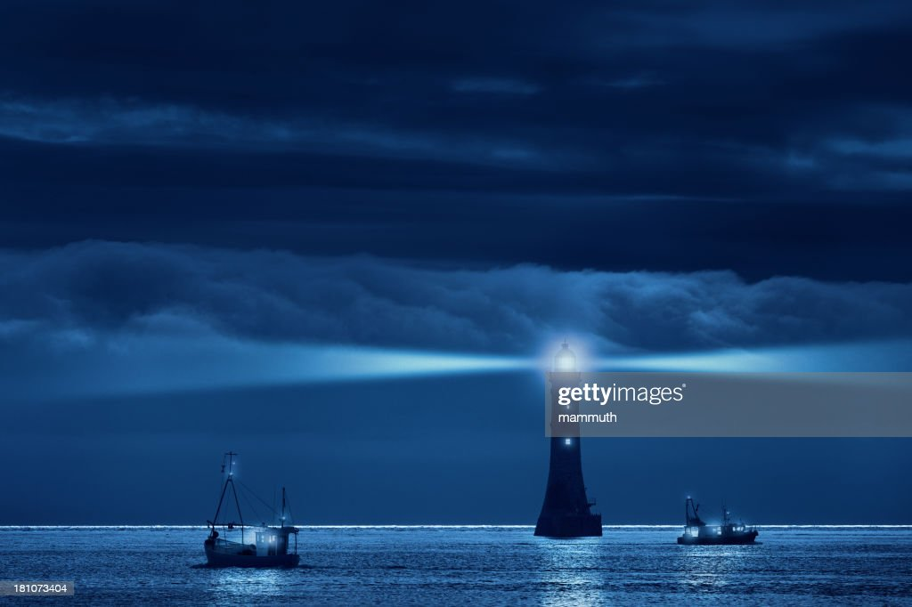 lighthouse and ships in the night : Stock Photo