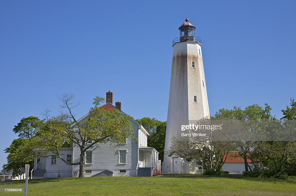 Lighthouse and white residence under blue skies