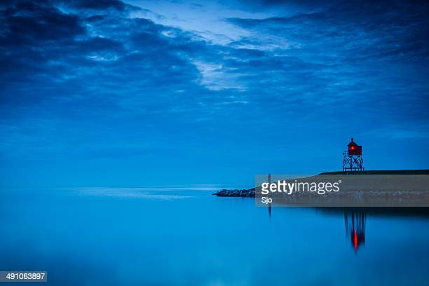 Lighthouse at a pier during twilight