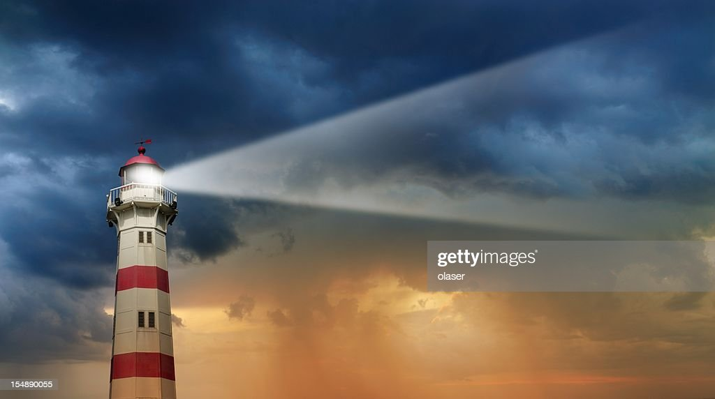 Lighthouse at dawn, bad weather in background : Stock Photo