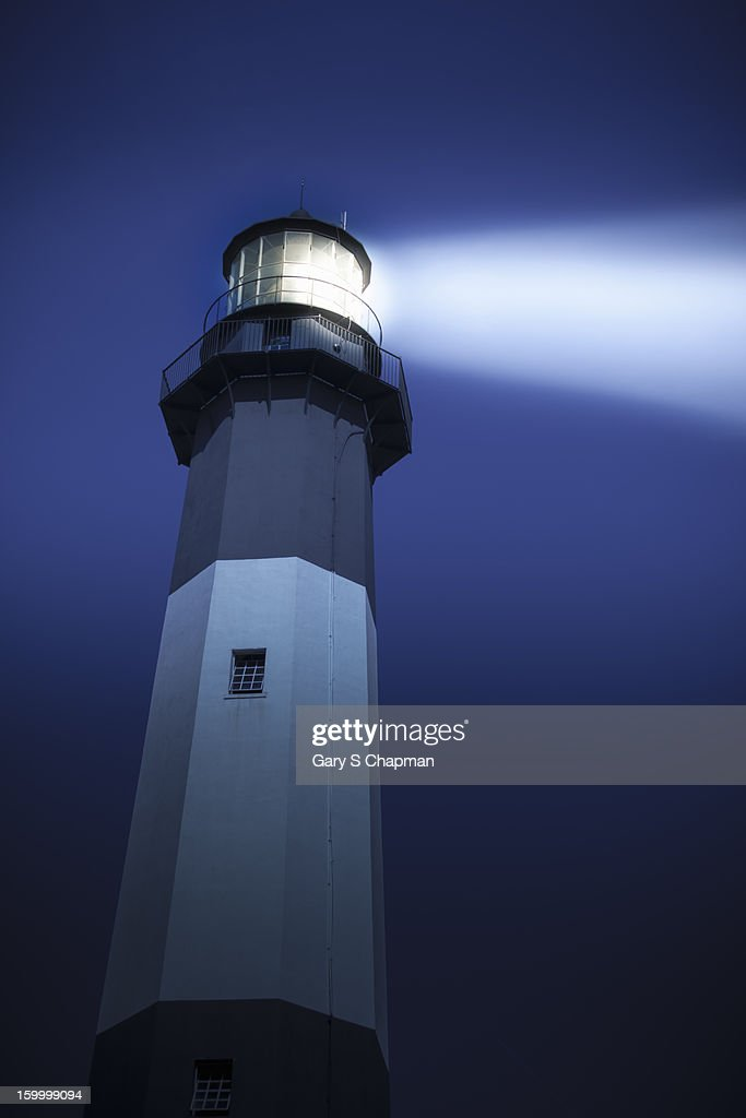Lighthouse at dusk with light on