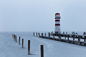 Lighthouse at sunrise with fog and rain during winter