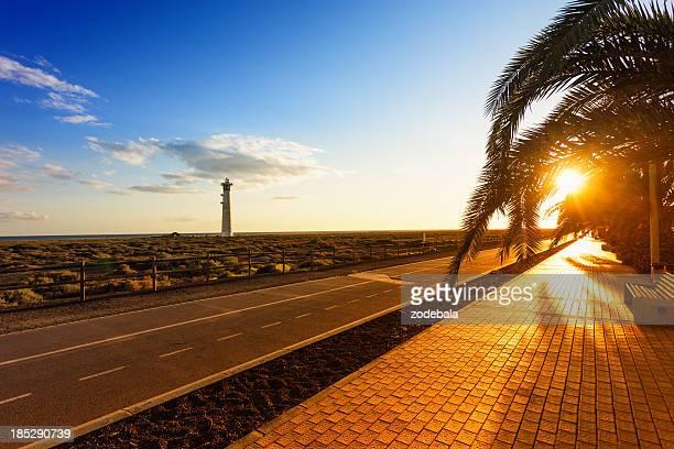 Lighthouse en la puesta de sol en la playa de isla de Fuerteventura, Islas Canarias