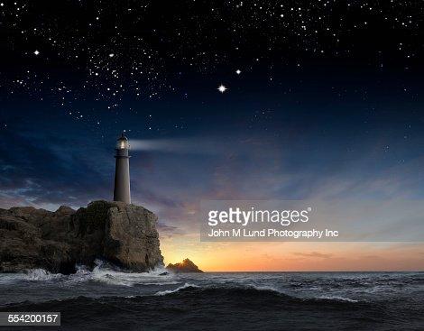 Lighthouse beaming over rocky ocean waves under sunrise sky