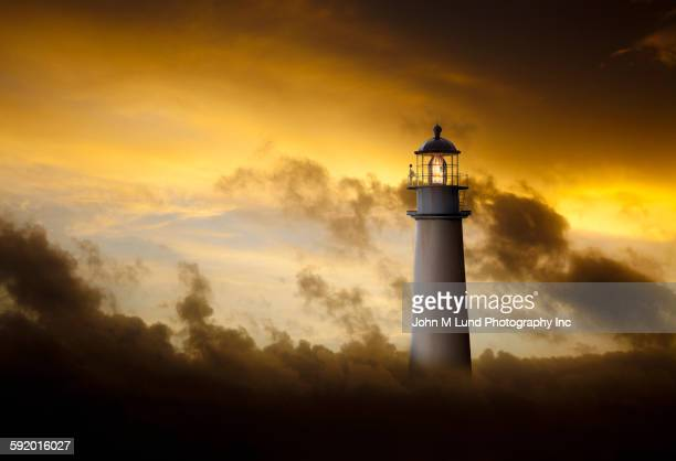 Lighthouse glowing under dramatic sky
